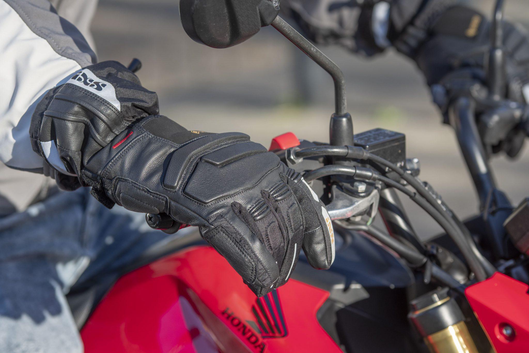 Handen met handschoenen die een motor vasthouden